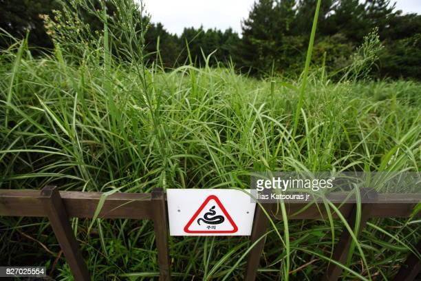 Korean warning sign of snakes in grassy hill