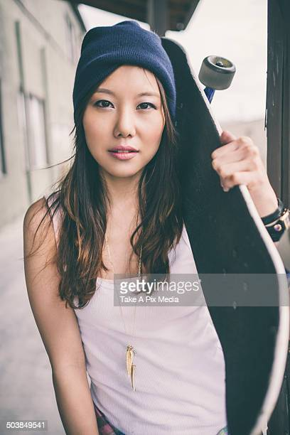 Korean woman carrying skateboard on city street