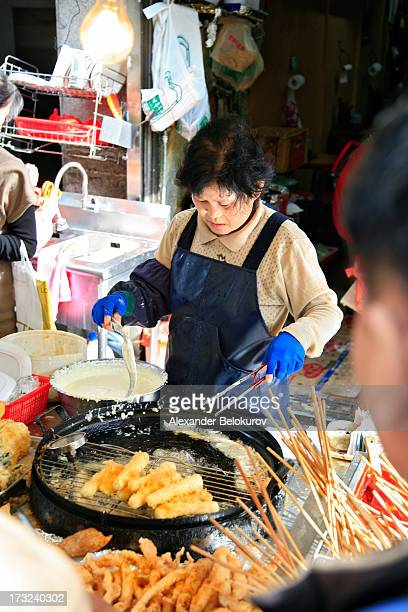 CONTENT] Korean woman cooking typical street food including deep fried fish and snacks in Busan South Korea She is a seller at a small street food...