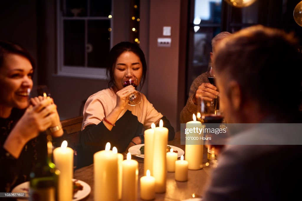Korean woman drinking wine with friends at dinner party : Stock Photo