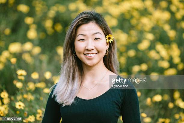 korean woman portrait in yellow flower covered field - korean ethnicity stock pictures, royalty-free photos & images
