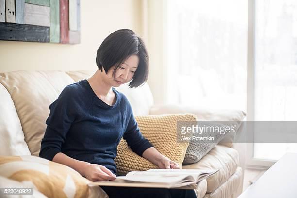 Coreano mujer leyendo el libro en la sala de estar