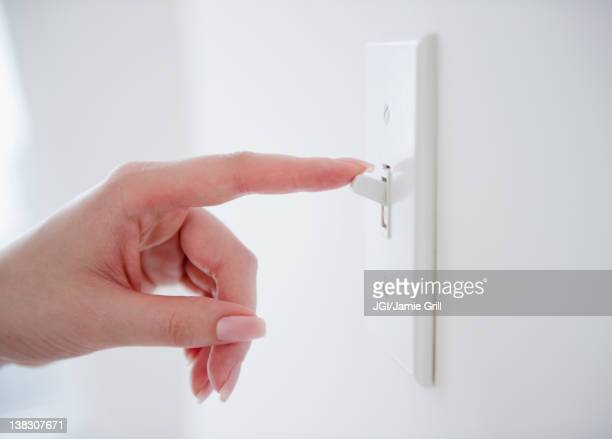Korean woman turning off light switch