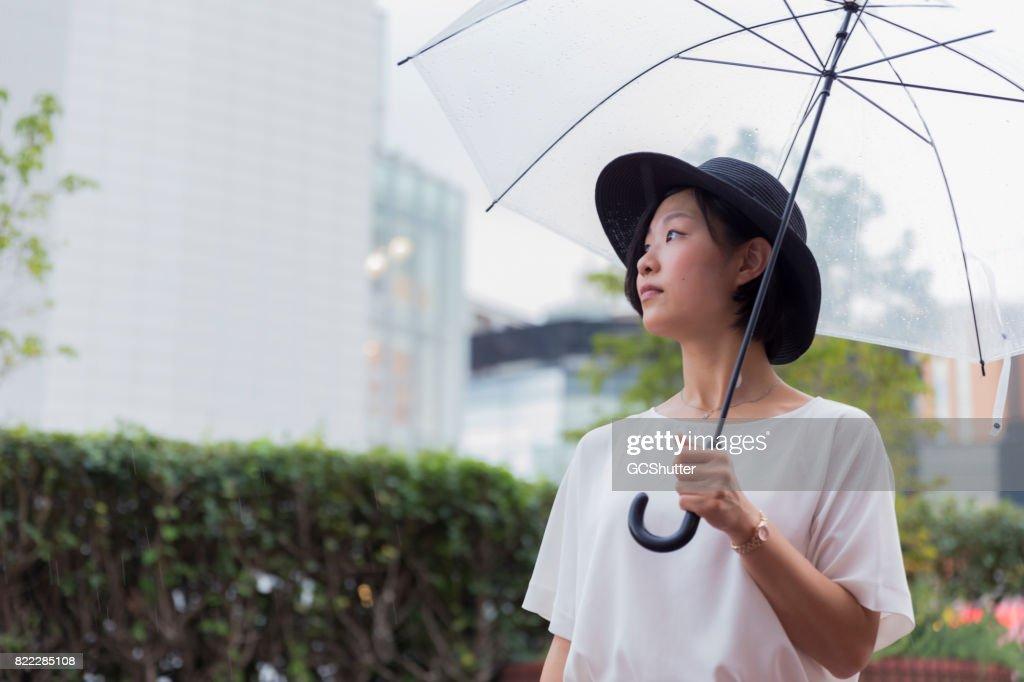 Korean woman walking in the rain : Stock Photo