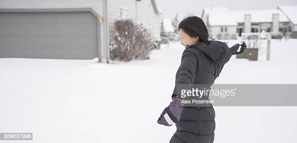 Korean woman walking outdoor under the snowfall