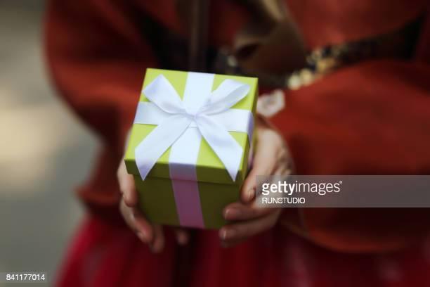Korean woman wearing hanbok is holding a gift box