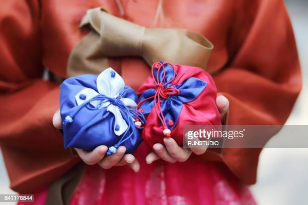 Korean woman wearing Hanbok is holding a gift