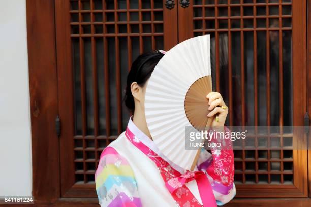 Korean woman wearing Hanbok is holding a Korean traditional fan