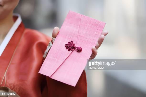 Korean woman wearing Hanbok is holding a voucher