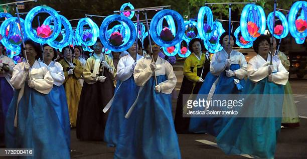 CONTENT] Korean women wearing traditional hanbok are carrying lotus lanterns in a parade in the evening to celebrate Buddha's birthday