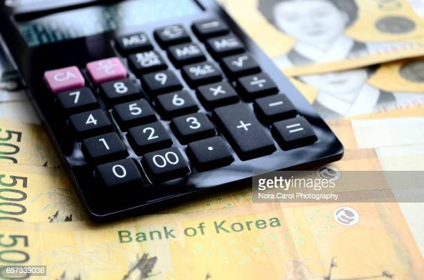 korean won currency with calculator - korean currency stock photos and pictures