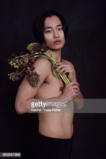 Korean young adult male in studio holding flowers
