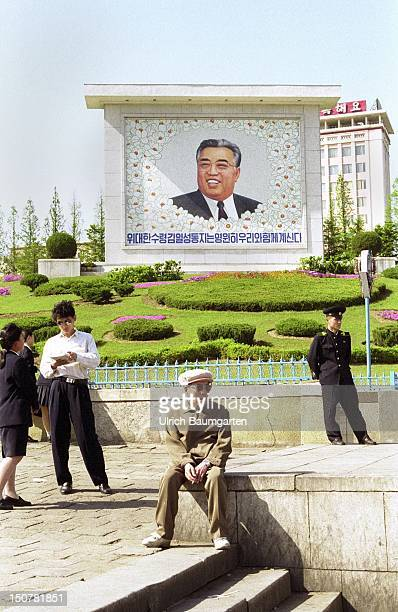 Koreans on a square in front of a picture of Kim Il Sung in Pjoengjang capital city of the democratic people`s republic of Korea