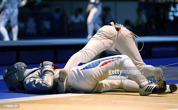 Korea's Kim JiYeon and France's Cecilia Berder fall during the women's individual sabre qualification round at the 2013 World Fencing Championships...