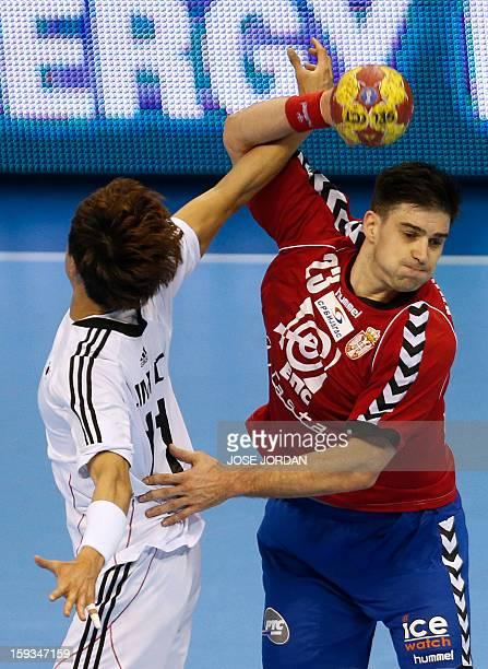 Korea's wing DukJun Lim vies with Serbia's back Nenad Vuckovic during the 23rd Men's Handball World Championships preliminary round Group C match...