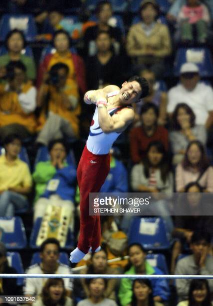 Korea's Yang Tae Seok performs on the high bar during the Artistic Gymnastics Men's Team Finals 01 October 2002 at the 14th Asian Games in Busan,...