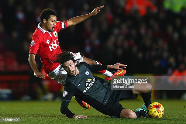 Korey Smith of Bristol City is tackled by Christian Burgess of Peterborough United during the Sky Bet League One match between Bristol City and...