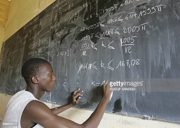 A student works on a mathematics problem in a Khorogo high school in the northern zone of Ivory Coast controlled by the New Forces 13 September 2005...