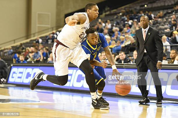 Kory Holden of the Delaware Fightin' Blue Hens dribbles by Nick Harris of the Charleston Cougars during the 1st round of the Colonial Athletic...