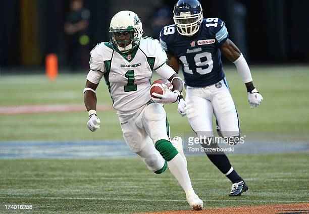 Kory Sheets of the Saskatchewan Roughriders carries the ball during CFL game action as Jalil Carter of the Toronto Argonauts chases from behind on...