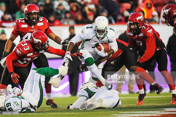 Kory Sheets of the Saskatchewan Roughriders splits the defense of Eric Fraser and Chris Randle of the Calgary Stampeders during a CFL game at McMahon...