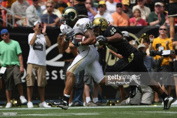 Kory Sperry of the Colorado State Rams carries the ball against Brad Jones of the Colorado Buffaloes at INVESCO Field at Mile High on September 1...