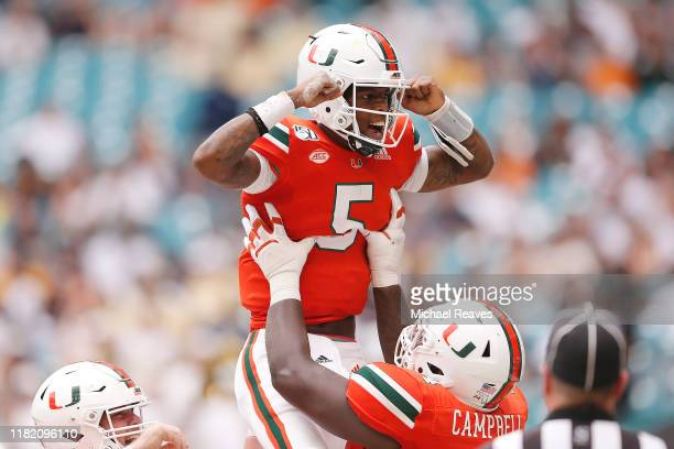 Kosi Perry of the Miami Hurricanes celebrates with teammates after a touchdown against the Georgia Tech Yellow Jackets during the first half at Hard...