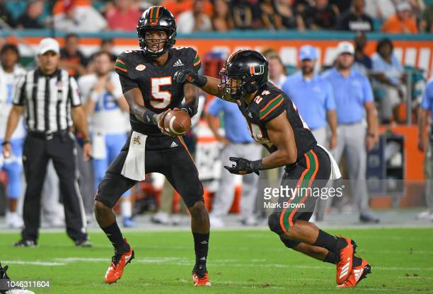 Kosi Perry of the Miami Hurricanes hands the ball to Travis Homer against the North Carolina Tar Heels at Hard Rock Stadium on September 27 2018 in...
