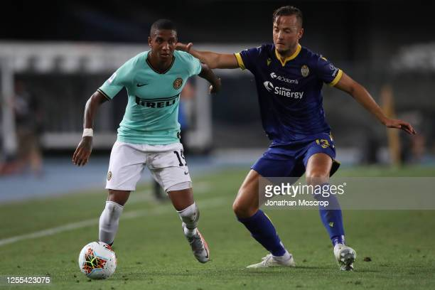 Kosovan defender Amir Rrahmani grapples with English midfielder Ashley Young during the Serie A match between Hellas Verona and FC Internazionale at...