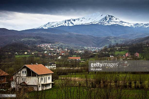 Kosovan landscape with farm and snow capped mountain