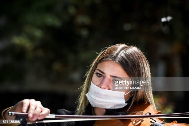 A Kosovar musician wearing face masks performes at the Mother Teresa square in Pristina on April 22 2017 as port of activities to raise awareness on...