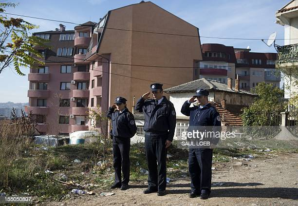 Kosovar police officials salute as US Secretary of State Hillary Clinton leaves on October 31 2012 the SaintNicholas Orthodox Church in Pristina...