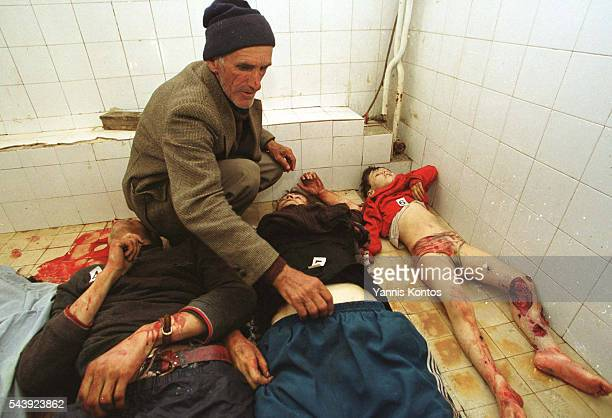 Kosovar refugee trying to identify members of his family in the hospital morgue.