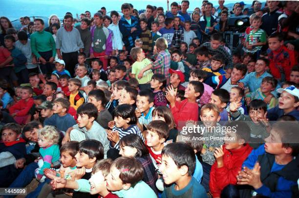 Kosovar refugees a watch movie featuring actor Charlie Chaplin at a camp for Kosovar refugees June 15, 1999 in Cegrane, 50 miles outside Skopje,...