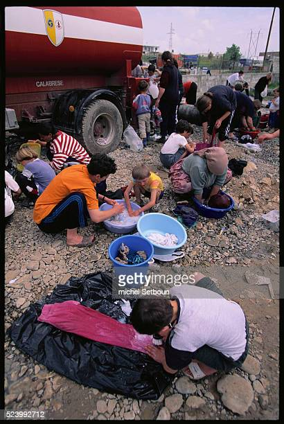 Kosovar refugees clean their laundry at Rushiubull a camp organized by the Italians   Location near Durres Albania