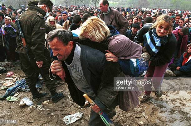A Kosovar woman overcome by heat and exhaustion is carried out of the squalid Blace refugee site in Macedonia April 5 at the border with Kosovo where...