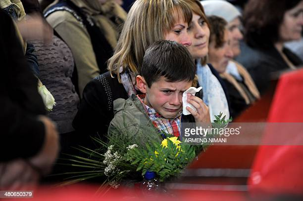 A Kosovo Albanian child cries over the coffins containing remains during a funeral ceremony in the town Suva Reka on March 26 2014 for the 27 Kosovo...