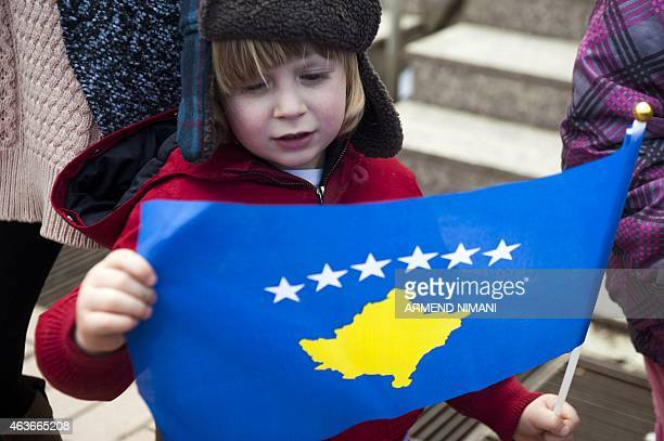 A Kosovo Albanian child holds a flag of Kosovo on the 7th anniversary of Kosovo's declaration of independence from Serbia in Pristina on February 17...