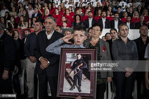 A Kosovo Albanian child holds the portrait of his relative during a funeral ceremony for eight Albanians who were killed during fighting with...