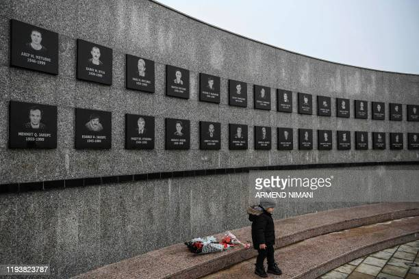 Kosovo Albanian child walks past a memorial dedicated to the victims of the Racak massacre on January 15, 2020 in the village of Racak. - In 1999,...