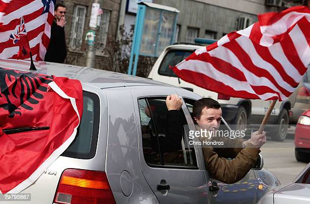 A Kosovo Albanian man displays American and traditional Albanian flags out of a car February 16 2008 in Pristina Serbia Kosovo Albanians are rabidly...