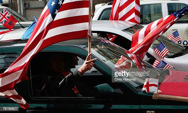 A Kosovo Albanian man waves American and traditional Albanian flags out of a car February 16 2008 in Pristina Serbia Kosovo Albanians are rabidly...