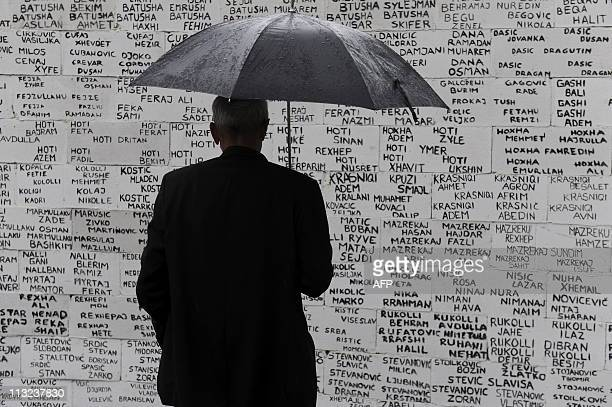 A Kosovo Albanian men stands in front of a wall depicting the names of missing people since the 199899 conflict in Kosovo during the Day of Missing...