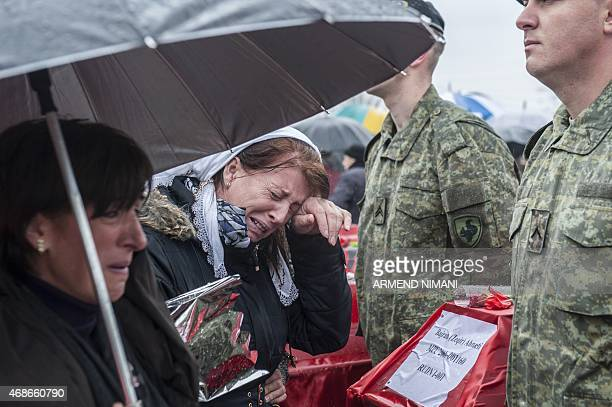 A Kosovo Albanian woman cries next to a coffin draped with the Albanian flag containing the remains of a war dead during a funeral ceremony in the...
