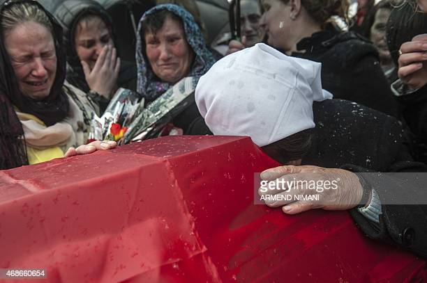 A Kosovo Albanian woman mourns over a coffin draped with the Albanian flag containing the remains of a war dead during a funeral ceremony in the...