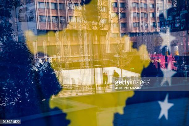 TOPSHOT Kosovo Albanians are reflected in a window decorated with the Kosovo flag in Pristina on February 16 2018 Kosovo marks the 10th anniversary...