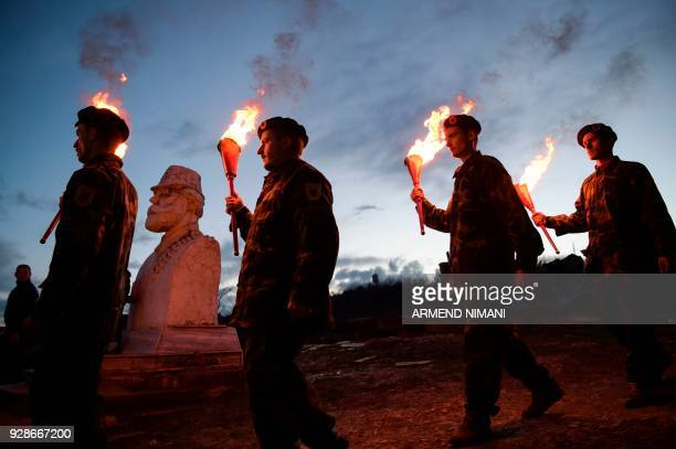 TOPSHOT Kosovo Albanians dressed in military costumes carry torches during a bonfire ceremony marking the 20th anniversary of the killing of Kosovo...