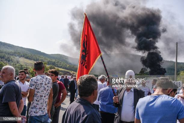 Kosovo Albanians gather around a barricade and smoke billows from burning tires as they block on September 9 2018 access to a village due to be...