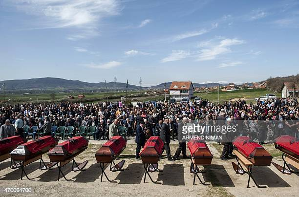 Kosovo Albanians pay their respect near coffins draped with the Albanian flag which contain the remains of 21 Kosovo Albanians allegedly killed by...