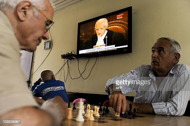 Kosovo Albanians play chess and watch the television in Pristina on July 22 2010 as the ICJ renders its decision on the legality of Kosovo's...
